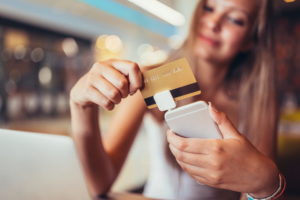 Woman in cafe making mobile payment with credit card