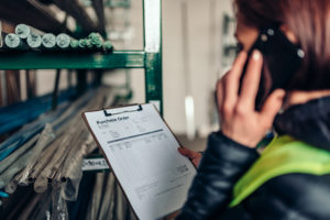 Warehouse clerk using phone and looking at purchase order