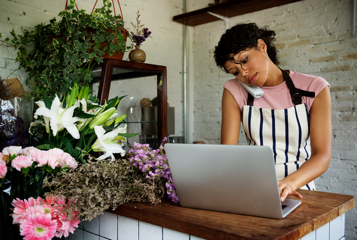 Woman on the phone and computer working in a flower shop