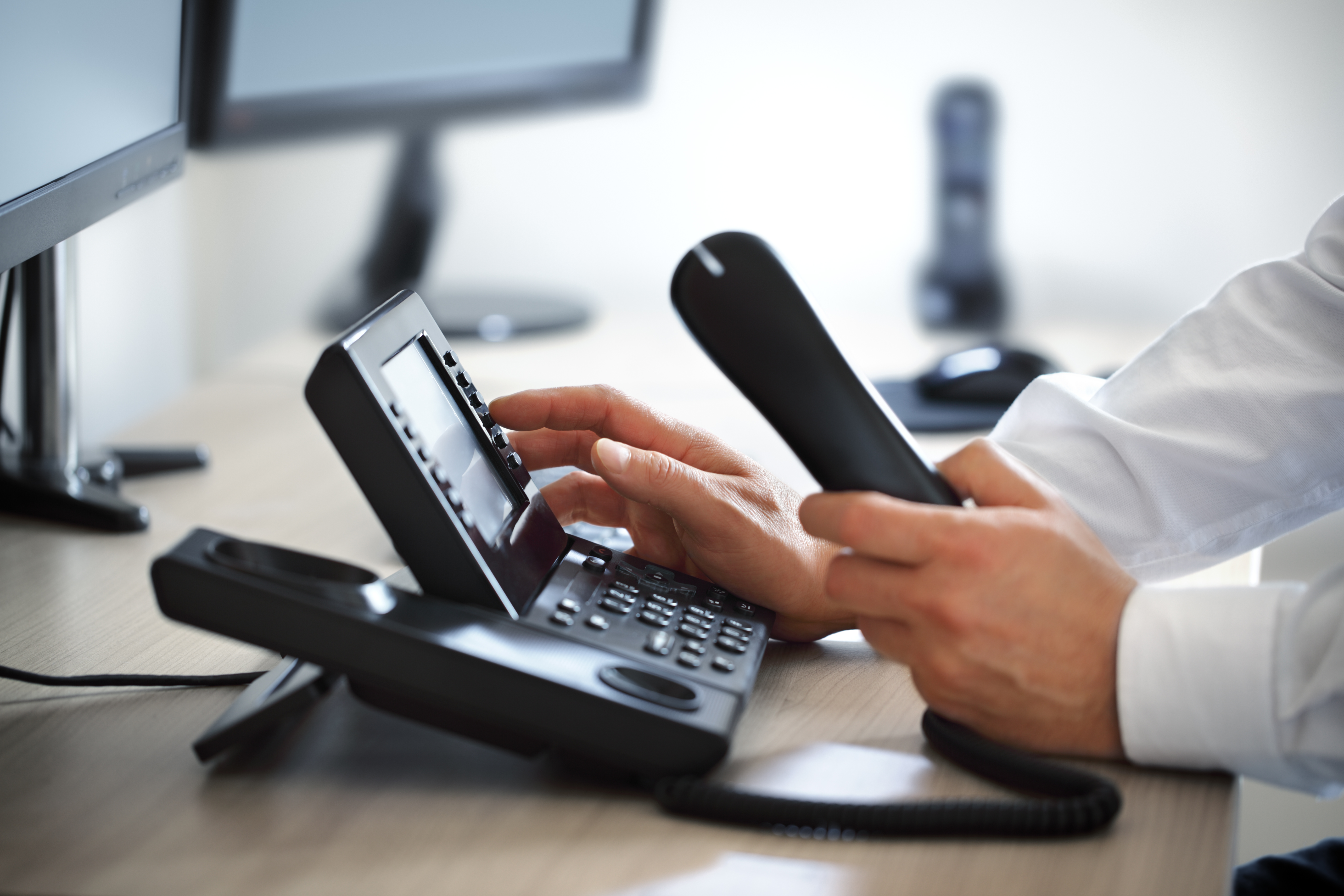 person dialing voip phone
