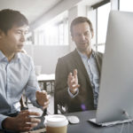 Two guys looking at web hosting plans