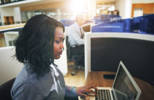 Young black woman with shoulder-length black hair types on a silver laptop in an office