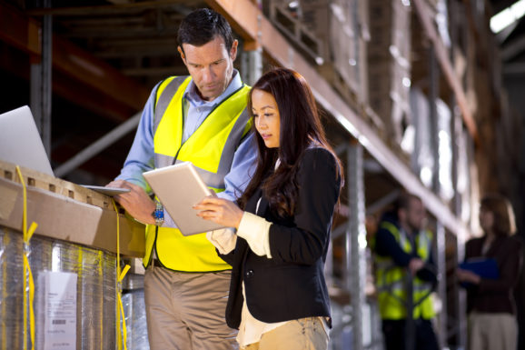 Illustrative image of a man and woman checking inventory levels in a warehouse.