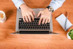 Picture of a man typing on a laptop